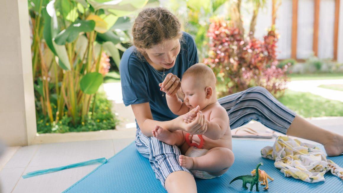 Maman qui joue avec son bébé sur la terrasse sous la pergola